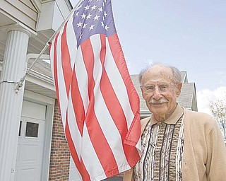 Ray Braidich, a World War II veteran, stands by the American flag mounted outside his home at Shepherd of the Valley-Poland. Braidich thinks there should be a more-dignified vessel in which to burn worn flags, noting that a trash can or burn barrel is often used in flag-disposal ceremonies.