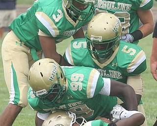 URSULINE - Quarterback Luke Petro is buried under the Ursuline defense (25) Tramain Thigpen, (99) Khallid Pierce, (5) Jesse Curry (3) Kevin Cylar and (33) Jeff Podolsky Saturday afternoon. - Special to The Vindicator/Nick Mays