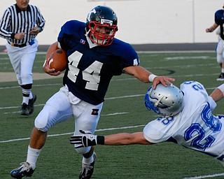 Warren JFK running back #44 James Coates stiff arms the Hubbard tackler #28 Kory Hopkinson.