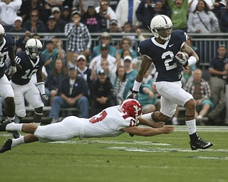 ROBERT K. YOSAY | THE VINDICATOR..SLIPPIN  away - PSU #2 Chaz Powell almost gets taken down by YSU #13 Stephen Blose as PSU runs back a kickoff to put PSU in the lead.YSU  LOSES 44-14   PENN STATE at BEAVER STADIUM IN HAPPY VALLEY.-30