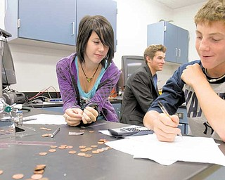 Junior Amanda Carlisle and sophomore Austin Beil practice taking precise measurements to determine the thickness of a penny and using indirect measurements to find the thickness of aluminum foil during chemistry class at Poland Seminary High School. After four years, all fi ve of the high school's science labs have been renovated.