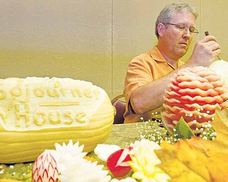 Ron Roberts, of Manic Organics Decorative Fruits and Vegetables, carves a watermelon as a finished watermelon obstructs the view and a squash cared for the event sits nearby, during the Seventh Annual Chef's Secrets Event to benefit the Sojourner House at the MetroPlex on Sunday afternoon..