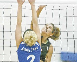 Mineral Ridge's Paige Rassega spikes the ball as Jackson-Milton's Ashley Staton (2) defends during Monday's match in North Jackson. Mineral Ridge remained unbeaten in 10 matches with a three game victory.