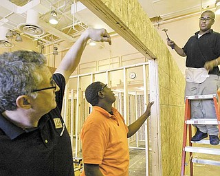 Choffi n Career and Technical Center construction-technology students Jhordan Jackson, center, and Laquail Brooks, both juniors, under instruction from teacher Kevin Sinkele , left, work on a house for Habitat for Humanity of Mahoning County.
