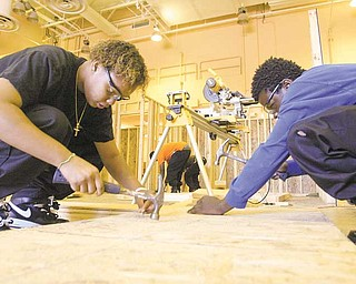 Juniors Eva Baker, left, and Aaron Clinkscale, with Choffin's construction technology program work on the house, which will become home to a Struthers family.