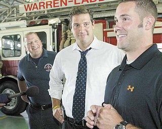 Jeremy Rodgers, right, a laid-off Warren firefighter, is all smiles after an announcement from U.S. Rep. Tim Ryan of Niles, D-17th, center, that the city fire department is getting a nearly $5 million federal grant to recall laid-off firefighters and hire new ones. At left is Marc Titus, president of the firefighters union. The announcement was made Wednesday at the central fire station in downtown Warren.