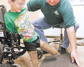 """Nicholai """"Kolya"""" Denykin, 10, of the Renewal Orphanage in Dimitrov, Russia, undergoes a fitting for prosthetic legs with Craig Svader of Advanced Anatomical Design, licensed prosthetic, orthotic and pedorthic professionals in Canfield and Girard. Kolya was born without legs below the knees."""