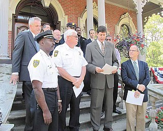 Law-enforcement officers and others who carried out the Violence and Gun Reduction Interdiction Program law-enforcement initiative this summer in the Mahoning Valley stand on the front steps of Warren City Hall during a press conference to declare that V-GRIP was an unqualified success, taking more than 150 firearms off the street and resulting in the arrest of 600 people. Shown in the front row Thursday are, from left, Youngstown Police Chief Jimmy Hughes; Warren Police Chief Tim Bowers; Steven M. Dettelbach, the U.S. Attorney for the Northern District of Ohio; and Warren Mayor Michael O'Brien.