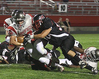 FOOTBALL - (30) Zach Miller leans for yardage as (50)David Benedis maks the stop Friday night in Campbell. - Special to The Vindicator/Nick Mays