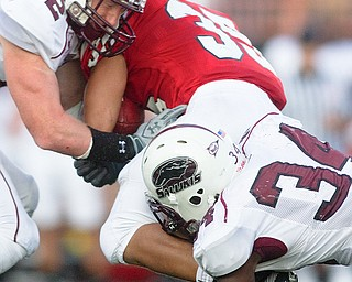 Geoffrey Hauschild|The Vindicator.Southern Illinois' Brad Briggs (12) and Jayson DiManche (34) bring down YSU's Jamaine Cook (35) during the second half of a game at Youngstown State University's Stambaugh Stadium on Saturday afternoon.