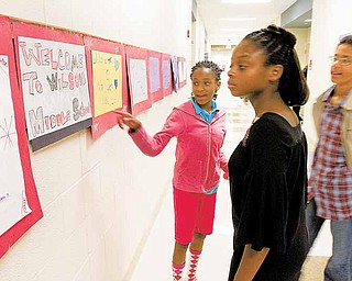 Sixth-graders Rayonna Abron-Booth, 11, left, and Monique Abron, 10, along with Tyler Abron, 14, check out artwork created by Rayonna during the ribbon-cutting ceremony and open house at the new Woodrow Wilson Middle School on Sunday afternoon.