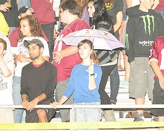 Dorie Chevlen a senior from Liberty High School trying to keep dry while cheering on the Leopards