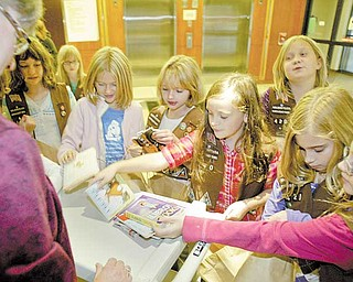 DeAnne Bunevich,  child-life specialist at Akron Children's Hospital, accepts a donation of books from Girl Scout Troop 420 of Canfield.  Bunevich said she suggested that the troop donate small, chunky pictures books with cardboard pages for younger children.