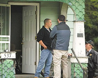 Police search the home at 537 Garfield St., off Glenwood Avenue, Tuesday afternoon. One man was taken into custody in the shooting death of Thomas J. Repchic, 74.
