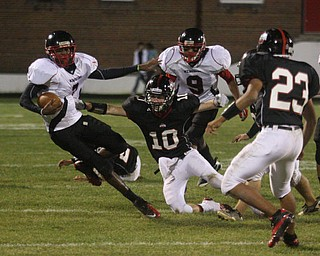 FOOTBALL - Lester Hughes tries to escape the grasp of (10) Zach Penick Friday night in Salem. (9) Dennis Williams and (23) Mike Crittenden get in on the play. - Special to The Vindicator/Nick Mays