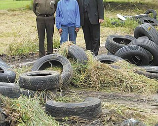 John Lesnansky, left, Helen Jackson and the Rev. Nicholas Mancini survey tires that will be cleaned up on Wilson Avenue across from St. Stephen of Hungary Church. The former Lewis Auto Body shop has been a popular illegal dumping ground since it closed in the 1970s.
