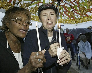 William d Lewis The Vindicator  Emma Nelson, left, of youngstown and sue Vitale of Boardman hold candles at a rally Saturday outside St Dom's church. The had never met before the rally.