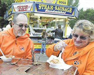 The Oktoberfest wouldn't be complete without food, and James and Charlotte Gosnell of Howland sample some. James Gosnell said they attended to help pick up the economy. About 10,000 people attended the annual event in Boardman Township Park on Sunday.