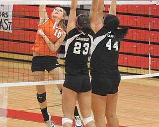 VOLLEYBALL - (10) Kylie Kohler of Springfield spikes the ball as (23) Hannah Milstead and (44) Mary-Kate Andrews go for the block Monday night. - Special to The Vindicator/Nick Mays