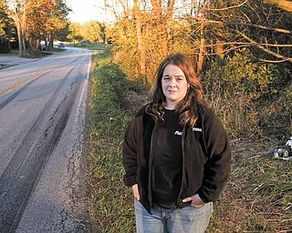 Lindsey Baird stands along a bend in Columbiana Road (County Road 62) near the intersection with Kibler Road. Baird lives at the curve and is concerned about the number of accidents at that location — five crashes this year, one of them fatal. Over Baird's shoulder is a memorial for Matthew A. Timmins, 22, who died from injuries sustained in a two-vehicle accident at the bend Sept. 26.