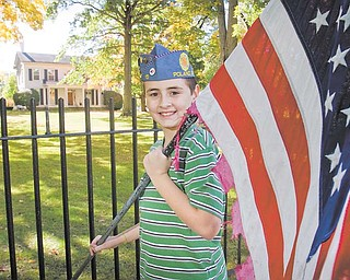 Jeffrey Vrabel Jr., 11, of Poland, displays one of the tattered American flags that will be retired as part of the Flags Over Poland fundraiser conducted by the Sons of the American Legion Squadron 15. The group hopes that 28 new American flags will be in place in front of Poland Village Hall on South Main Street by Veterans Day, Nov. 11..