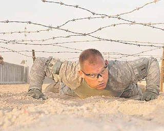 Staff Sgt. James Balog, a Chaney High School graduate, crawls under barbed wire as part of a physical assessment course. Balog won the competition and is the U.S. Division-South Noncommissioned Officer of the Quarter..