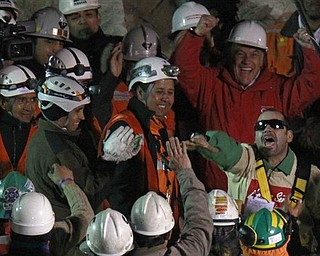 Chile's President Sebastian Pinera, top right, cheers as rescued miner Mario Sepulveda Espina, right, salutes after  being rescued from the the collapsed San Jose gold and copper mine where he was trapped with 32 other miners for over two months near Copiapo, Chile, early Wednesday Oct. 13, 2010.(AP Photo/Roberto Candia)