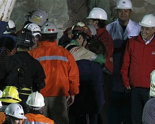 Chile's President Sebastian Pinera, right, looks on as  miner Florencio Antonio Avalos Silva embraces his wife Monica after he was rescued from the collapsed San Jose gold and copper mine where he was trapped with 32 other miners for over two months near Copiapo, Chile, early Wednesday, Oct. 13, 2010.(AP Photo/Roberto Candia)