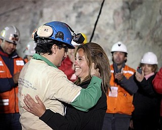 In this photo released by the Chilean government, miner Raul Bustos, left, embraces an unidentified woman after after being rescued from the collapsed San Jose gold and copper mine where he had been trapped with 32 other miners for over two months near Copiapo, Chile, Wednesday Oct. 13, 2010.  (AP Photo/Chilean Government, Hugo Infante)