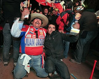 People celebrate the end of the successful rescue operation that freed 33 trapped miners from the San Jose mine in Copiapo, Chile, Wednesday Oct. 13, 2010. The 69-day underground ordeal reached its end Wednesday night after 33 trapped miners were hauled up in a cage through a narrow hole drilled through 2,000 feet of rock. (AP Photo/Martin Mejia)
