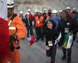 In this photo released by the Chilean government, family members approach the capsule containing miner Richard Villaroel as he is rescued from the collapsed San Jose gold and copper mine where he had been trapped with 32 other miners for over two months near Copiapo, Chile, Wednesday Oct. 13, 2010.  (AP Photo/Hugo Infante, Chilean government)
