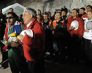 In this photo released by the Chilean Presidential Press Office, the last miner to be rescued, Luis Urzua, front row left, sings Chile's national anthem with Chile's President Sebastian Pinera and rescue workers after he was rescued from the collapsed San Jose gold and copper mine where he had been trapped with 32 other miners for over two months near Copiapo, Chile, Wednesday Oct. 13, 2010.  The 69-day underground ordeal reached its end Wednesday night after 33 trapped miners were hauled up in a cage through a narrow hole drilled through 2,000 feet of rock.  (AP Photo/Alex Ibanez, Chilean Presidential Press Office)