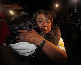 Maria Segovia, right, sister of freed miner Dario Segovia, embraces an unidentified person as relatives and friends of the freed 33 miners celebrate the end of the successful rescue operation at the camp outside the San Jose mine near Copiapo, Chile, Wednesday Oct. 13, 2010.  The 69-day underground ordeal reached its end Wednesday night after 33 trapped miners were hauled up in a cage through a narrow hole drilled through 2,000 feet of rock. (AP Photo/Natacha Pisarenko)