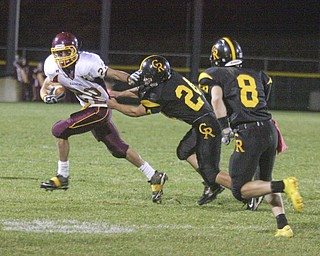 FOOTBALL - (22) Phillip Arsuffi tries to get away from (24) Craig Lower and (8) Jacob Danks Friday night at Crestview. - Special to The Vindicator/Nick Mays