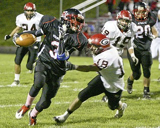 William D. Lewis|The Vindicator Campbell's Ja Les Hughes finds a hole and eludes Girard'sBryan Daugherty during 1 rst half action Friday at Campbell.