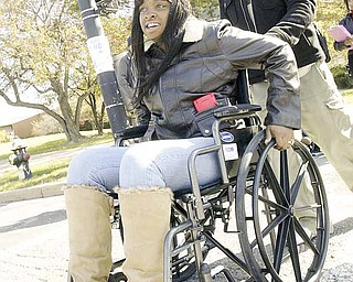 Ariel Holmes, a Youngstown State University student from Warren, wheels across Fifth Avenue with the help of Robert Martin, a physical-therapy student at the university. The pair participated Wednesday in the Where There's a Wheel There's a Way program.