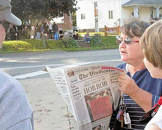 "Geoffrey Hauschild|The Vindicator                           .Carol Tigert (second from right) and her daughter Makenzie Tigert, 15, both of Niles, read an article in The Vindicator about the Holloween display featuring dead dolls as supporters of the display gather at its location across the street on Wednesday evening. ""Its just way over the line,"" said Carol, ""little kids don't need to be seeing theis added her daughter Makenzie."
