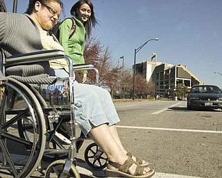 Brenda Wagner, a student at Youngstown State University, makes her way across Fifth Avenue with YSU physical-therapy major Kristie LaCivita. Wagner rolled across the busy road Wednesday morning as a participant in Where There's a Wheel There's a Way, an initiative by YSU's Physical Therapy Department. October is Physical Therapy Month.