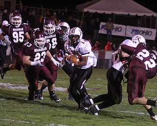 FOOTBALL - (14) Taron Montgomery gets away from the Boasrdman defense including (23) Nate Provanca and (58) Bergen Brown during their game Thursday night. - Special to The Vindicator/Nick Mays