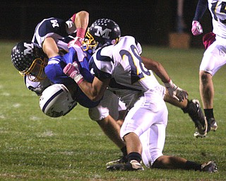 FOOTBALL - (1) Ryley Sheptock of Western Reserve is sandwiched by (13) Mike Helco and (28) Stephen Mohamed Friday night in Berlin Center. - Special to The Vindicator/Nick Mays