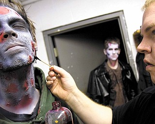 Josh Hamilton, of Salem, receives airbrushing from Joe Glenn in preparation for his zombie character whoweilds a chainsaw at the Canfield Scaregrounds on Thursday evening.