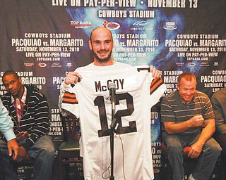 Kelly Pavlik, center, holds a Cleveland Browns' Colt McCoy jersey at a press conference.