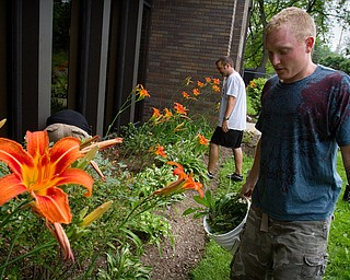 Geoffrey Hauschidl|The Vindicator.6.15.2010.OVTC resident Anthony Sanders works on weeding the outside of the OVTC building on the North Side of Youngstown. Scott Fabry is in the background.