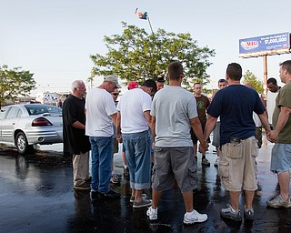 Geoffrey Hauschild|The Vindicator.6.18.2010.Members of OVTC pray in the parking lot during a carwash and crane fundraiser along U.S. 224 in Boardman.