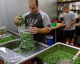 Geoffrey Hauschild|The Vindicator.8.5.2010.OVTC intern ,John Jones and resident Kevin McCoy work to package beans for freezing while in the OVTC's Hope Kitchen. The beans were donated from a local farmer.