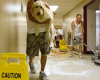 Geoffrey Hauschild|The Vindicator.8.6.2010.OVTC resident Anthony Sanders (right), works to remove carpeting from the residence hall at OVTC.