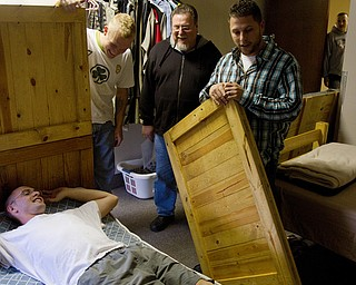 Geoffrey Hauschild|The Vindicator.10.14.2010.Dennis McKenney lies down on a newly assembled bed as student Anthony Sanders, Executive Director Roy Barnett and Director of Operations Bob Pavlich, work to create more space for future residents at Ohio Valley Teen Challenge.