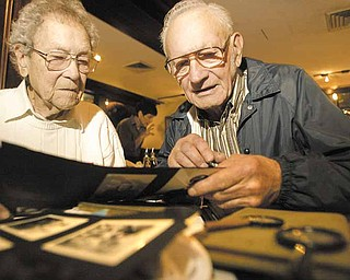 Charles Butler, 90, left, of Liberty, and Frank R. Swast, 85, of North Carolina, look over old World War II photos. Butler was Swast's commanding officer on a ship when they both served in the Navy. They haven't seen each other in more than 60 years. Efforts by Swast's family here helped bring them together for a reunion Wednesday at the Springfield Grille in Boardman.
