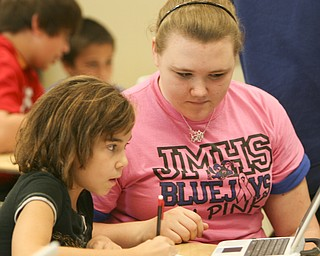 ROBERT K. YOSAY | THE VINDICATOR..Ninth graders at Jackson  Milton High School taught  fourth graders an interactive poetry lesson during a reading of The Raven by Edgar Allan Poe..Breanna Saunders  ( pink shirt ) 9th grade - asks questions  of Lindsey Osborne  4th grade -- to help her understand the poem ..  --30-.