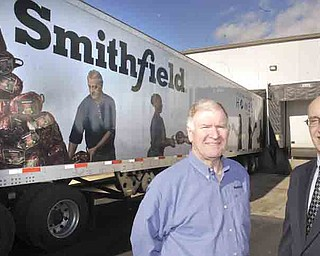 Dennis Pitman, left, Smithfield Foods' director of corporate communications, and Michael Iberis, executive director of Second Harvest Food Bank of the Mahoning Valley, stand beside an 18-wheeler that delivered 30,000 pounds of pork products donated to the food bank by Smithfield and the United Food and Commercial Workers Union.